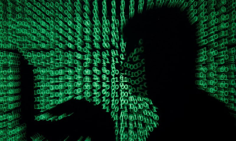 A man holds a laptop computer as cyber code is projected on him in this illustration picture. — Reuters/File