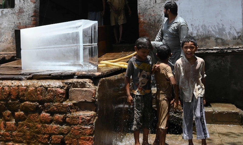 Children cool off next to an ice block at an ice factory in Lahore on June 9. — AFP