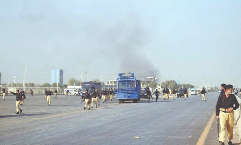 In this file photo, police arrive as smoke billows from buildings in Bahria Town amid protests. —PPI/File