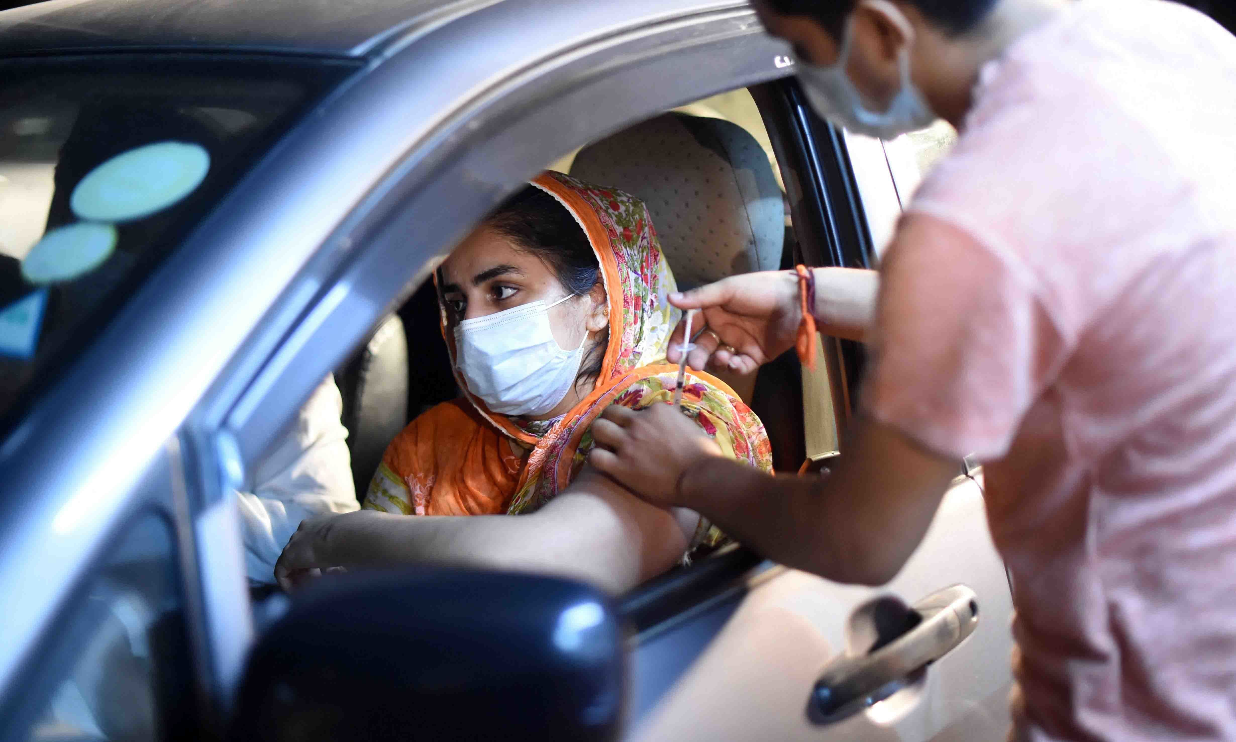 A woman receives the Sinopharm vaccine in the first drive-through vaccination centre, in Lahore on June 10. — AFP