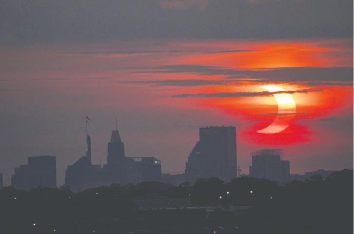 A PARTIAL solar eclipse over the skyline in Baltimore, in the US state of Maryland.—AP