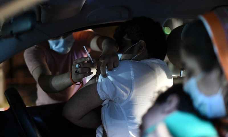 A man receives the Sinopharm vaccine in the first drive-through vaccination centre, in Lahore on June 10. — AFP