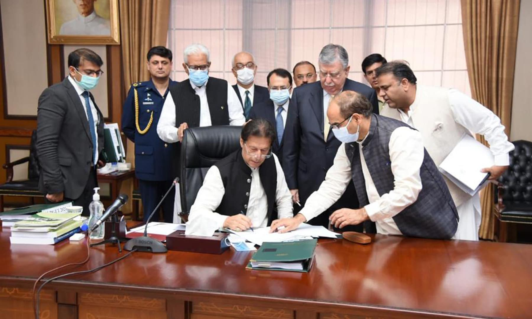 Prime Minister Imran Khan signs the Budgetary Proposals for FY2022 during a meeting of the federal cabinet in Islamabad on Friday. — PID