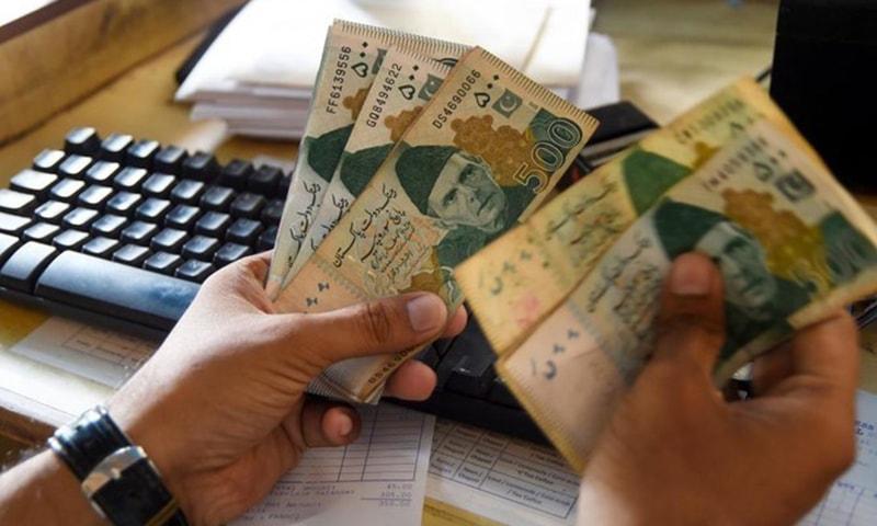 A man counts money at his shop in Karachi.— AFP/File
