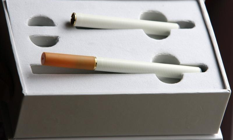 A woman displays a package of e-cigarette, an electronic substitute in the form of a rod, slightly longer than a normal cigarette. — Reuters