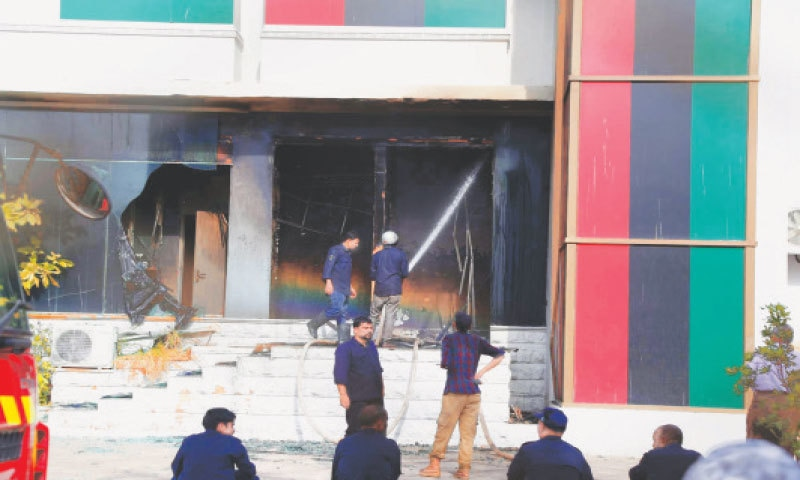 Firefighters hose down the site of the blaze at Bilawal House's media cell on Friday.—PPI