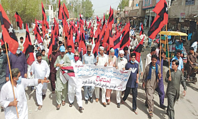 PROTESTERS march through a street in Kandhkot on Friday.—Dawn