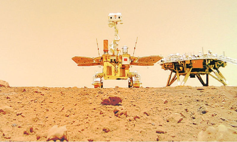 A photograph released by the China National Space Administration on Friday shows the rover (left) and the landing platform on the surface of Mars. —AFP