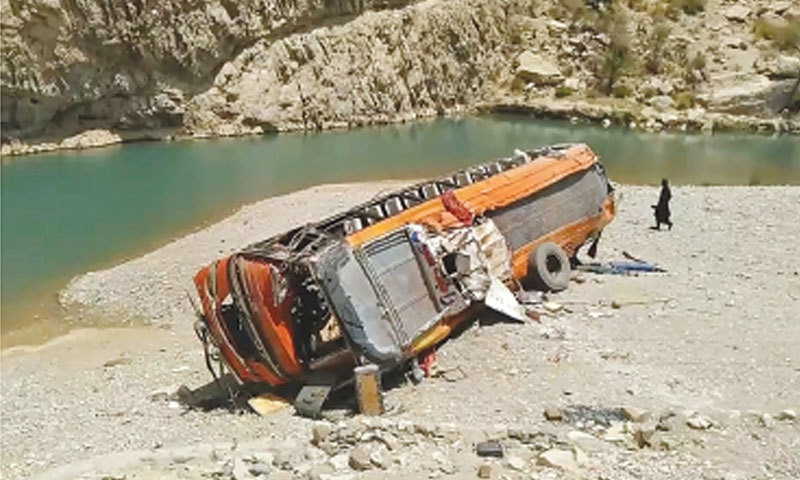 A man walks past the bus at the scene of the accident in Khuzdar on Friday.—AFP
