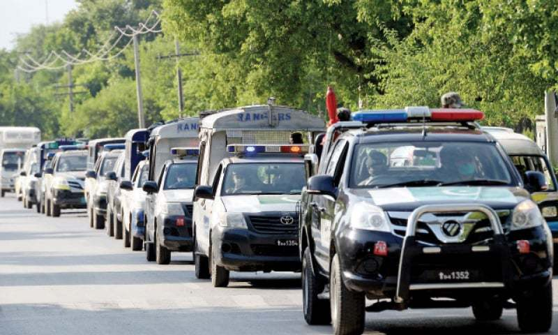 Security personnel pass through I-8 of Islamabad during a flag march in this file photo. — Photo by Mohammad Asim