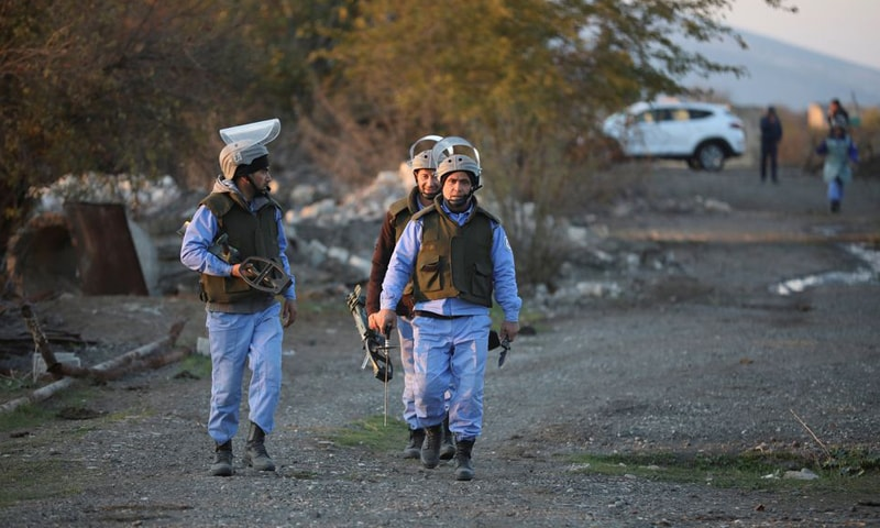 Azerbaijani service members walk during mine lifting in Agdam town in the region of Nagorno-Karabakh. — Reuters/File