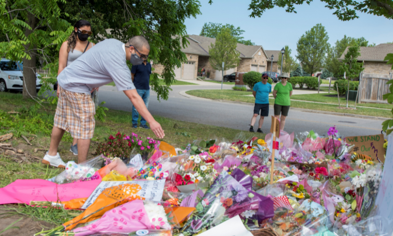 A person leaves a flower at a makeshift memorial at the scene where a Muslim family was killed in what police describe as a hate-motivated attack, at the London Muslim Mosque in London, Ontario on Saturday. — Reuters