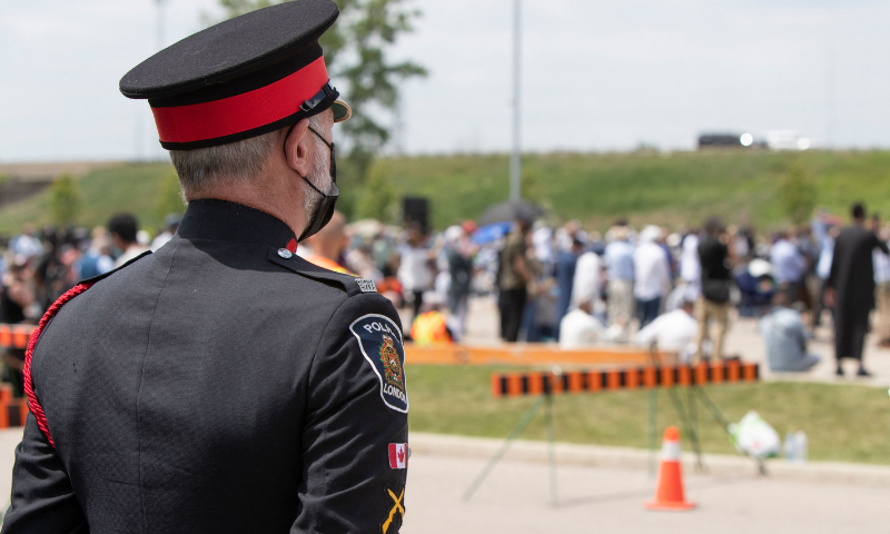 A police officer stands guard as people arrive at the Islamic Centre of Southwest Ontario on Saturday to pay their respects at the funeral of four members of the Afzaal Family, in London, Ontario. —