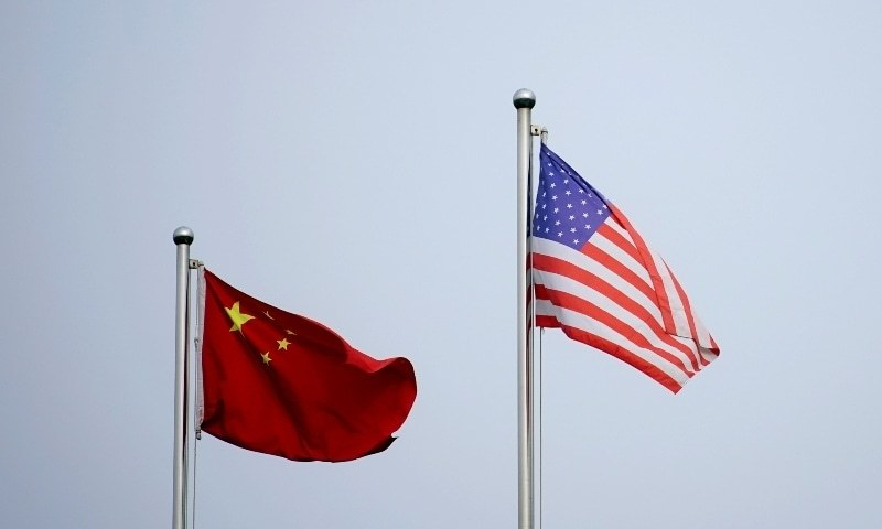 Chinese and US flags flutter outside a company building in Shanghai, China, April 14. — Reuters