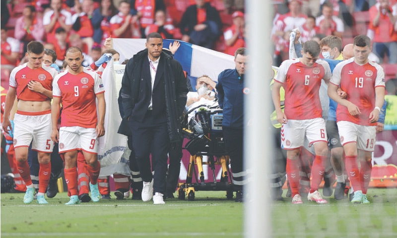 COPENHAGEN: Denmark players escort midfielder Christian Eriksen (C) as he is evacuated after collapsing on the pitch during the Group 'B' match against Finland at the Parken Stadium.—AFP