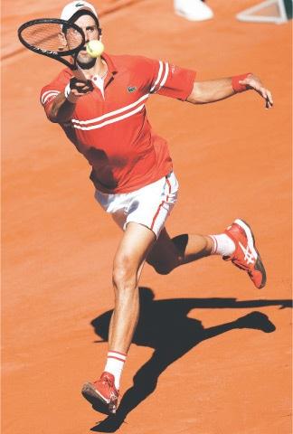 PARIS: Serbia's Novak Djokovic hits a return to Stefanos Tsitsipas of Greece during their French Open final on Sunday.—AP