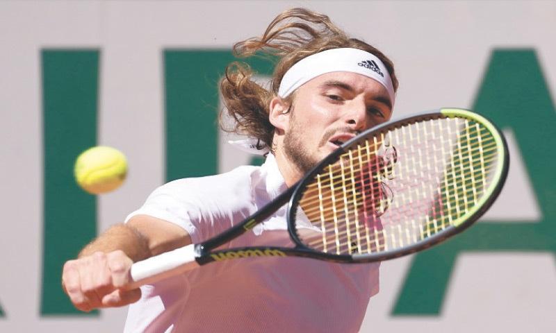 TSITSIPAS hits a backhand return to Djokovic at the Roland Garros Stadium.—AP