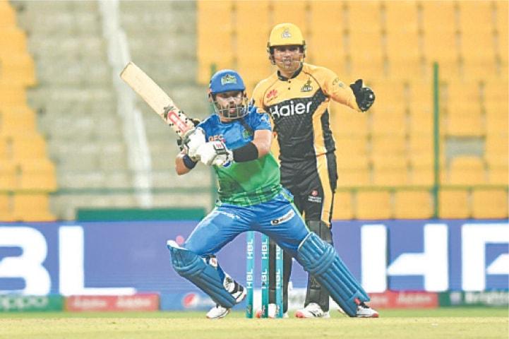 ABU DHABI: Multan Sultans captain Mohammad Rizwan plays a shot as Peshawar Zalmi wicket-keeper Kamran Akmal looks on during the HBL Pakistan Super League match at the Sheikh Zayed Stadium on Sunday night.—Courtesy PCB