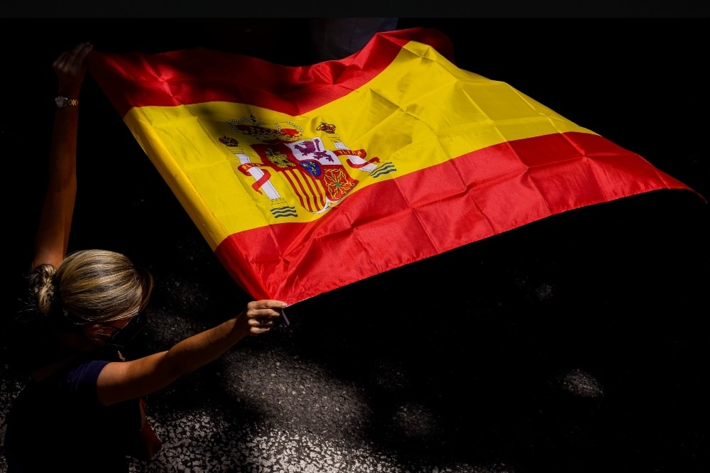 A woman holds the Spanish flag during a protest against the Spanish government's plan to issue pardons to a dozen imprisoned Catalan separatist leaders on June 13.  — AP