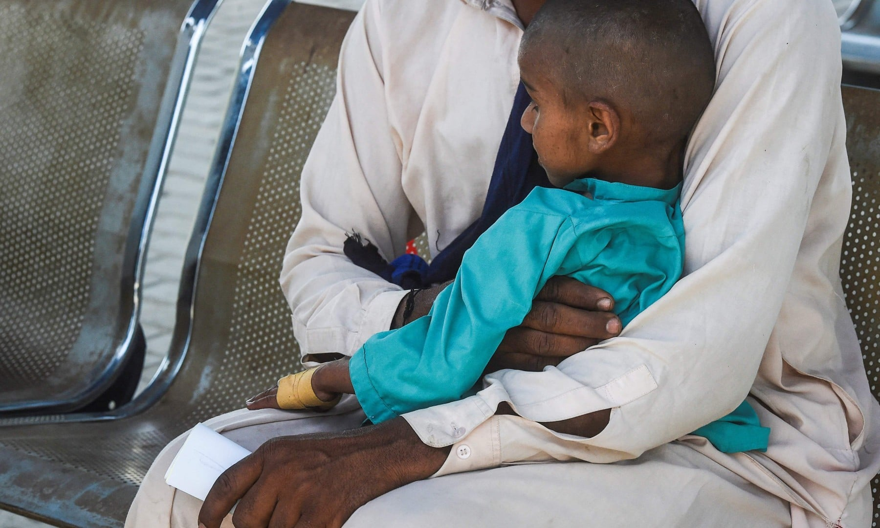 In this picture taken on March 25, a father and his HIV positive son wait for their turn at a treatment support centre in Ratodero. —  AFP