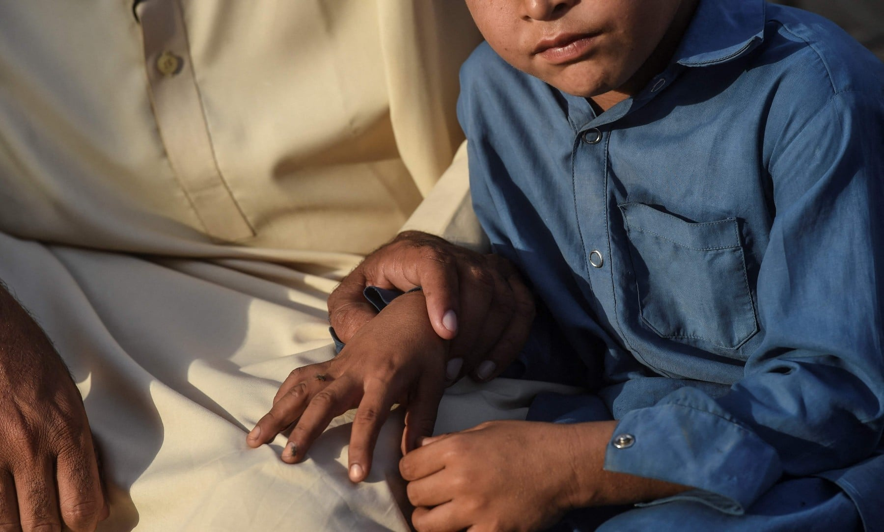 In this picture taken on March 25, Shahzado Shar (L) sits with his HIV positive son at their home in Subhani Shar village. —  AFP