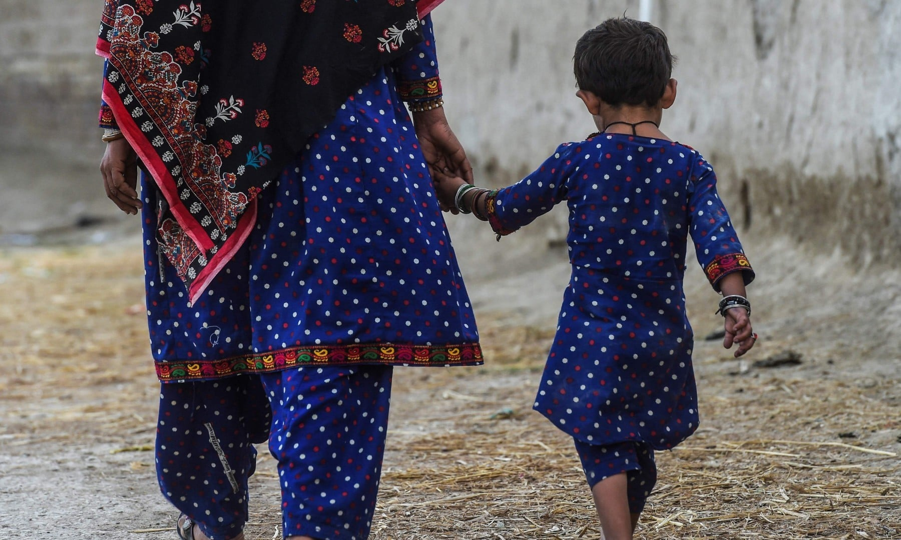 In this picture taken on March 25, Hakima Shar and her daughter, who are both HIV positive, walk outside their home in Subhani Shar village. —  AFP