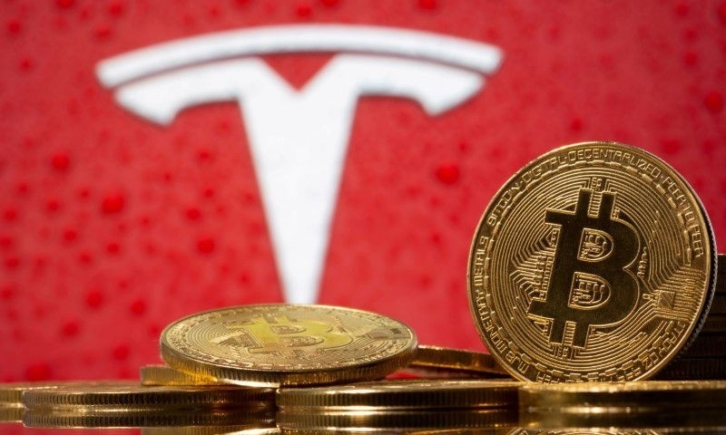 Representations of virtual currency Bitcoin are seen in front of the Tesla logo in this illustration taken, February 9. — Reuters