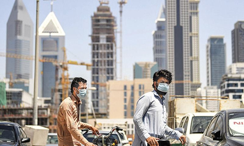 Migrant workers walk pushing bicycles along a street in Dubai's Satwa district in this file photo. — AFP