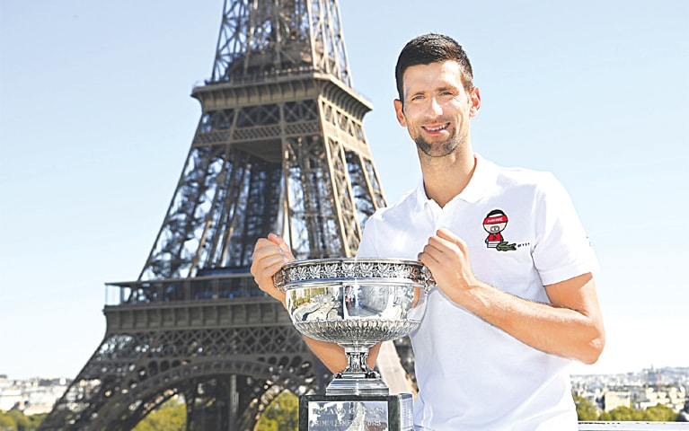 PARIS: Serbia's Novak Djokovic poses with the French Open trophy in front of the Eiffel tower during a photocall on Monday.—AP