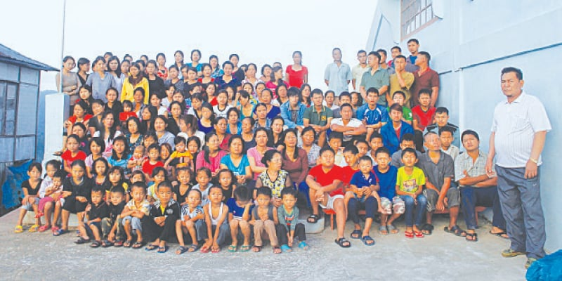A 2011 file picture shows members of Ziona's family posing for a group photograph outside their residence in Baktawng village.—Reuters