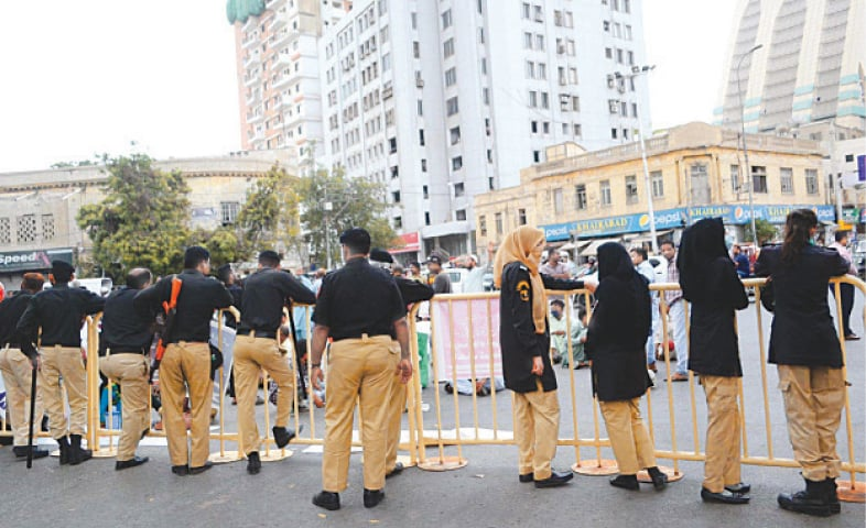 Residents of settlements along the Orangi and Gujjar nullahs protest outside the SC's Karachi registry on Monday against the demolition of their homes while security personnel stand alert.—PPI