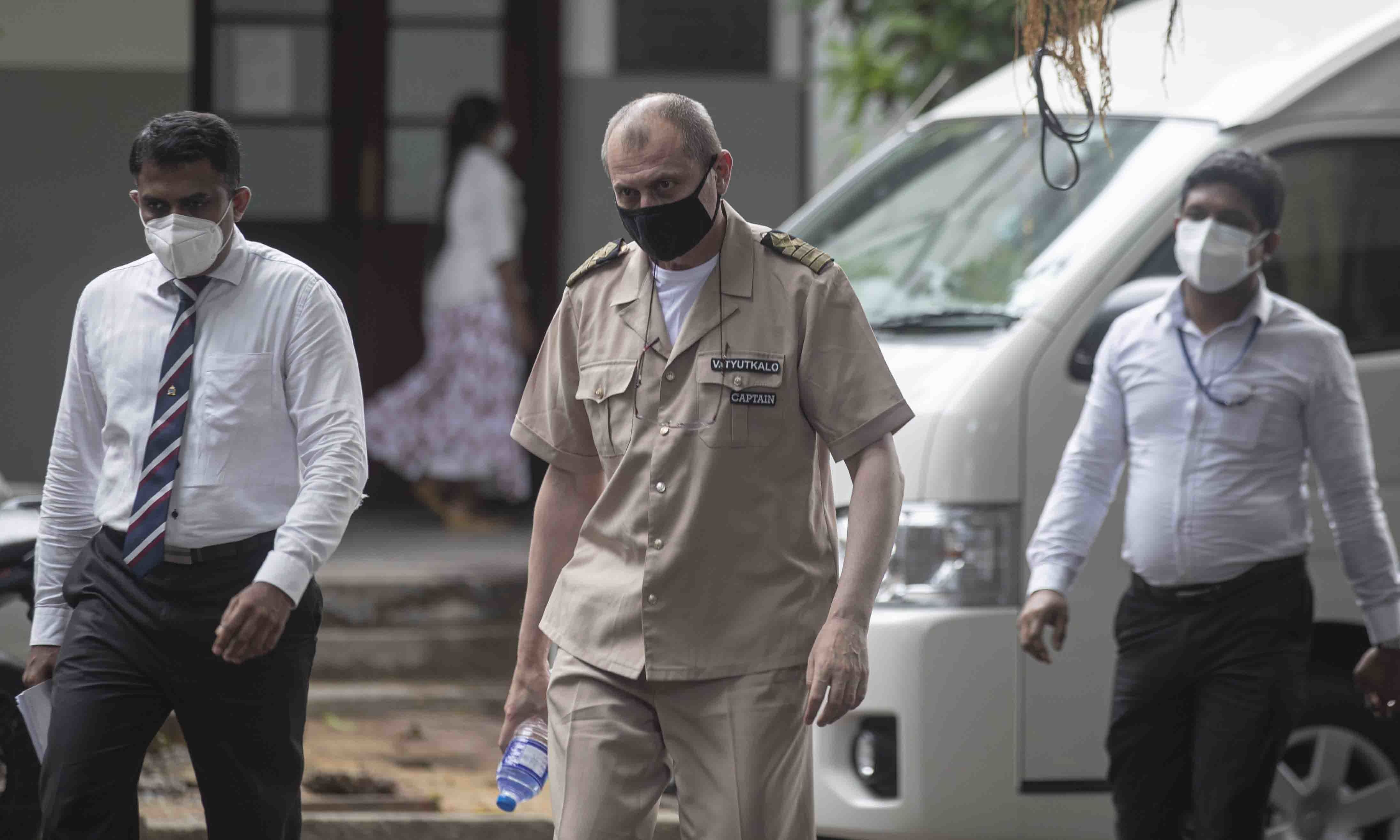 Sri Lankan police officers escort Russian Captain Tyutkalo Vitaly, center, of fire damaged container ship MV X-Press Pearl at a court before the hearing begins in Colombo on June 14. — AP