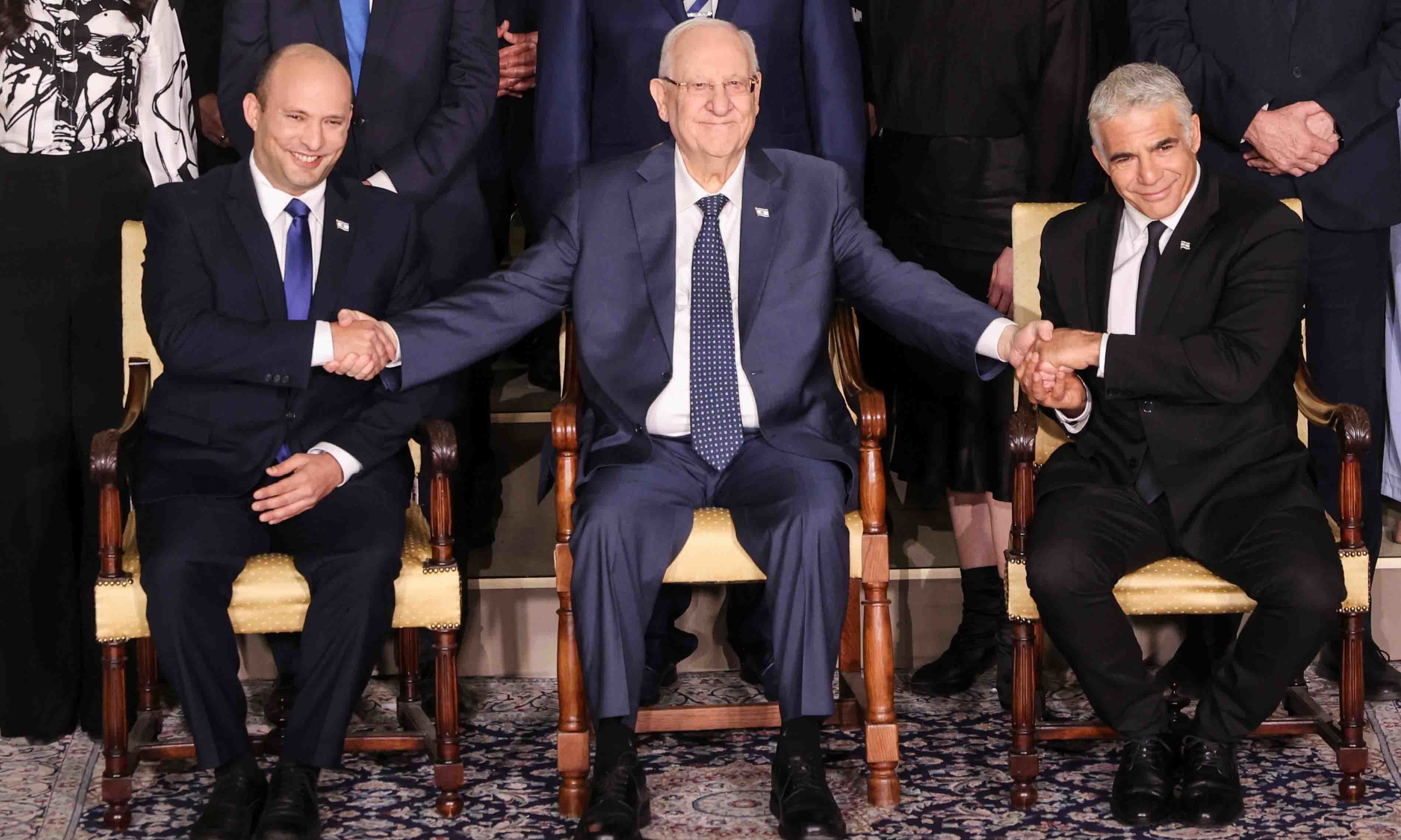srael's President Reuven Rivlin between Prime Minister Naftali Bennett and Foreign Minister Yair Lapid as they pose for a group photo with ministers of the new Israeli government, in Jerusalem on June 14. — Reuters