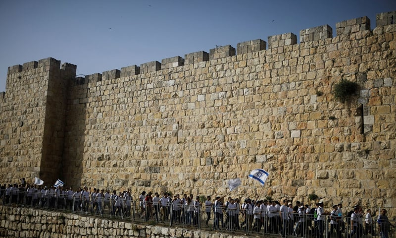 Youths wave Israeli flags during a parade marking Jerusalem Day amid Israeli-Palestinian tension as they march along the walls surrounding Jerusalem's Old City on May 10, 2021. — Reuters