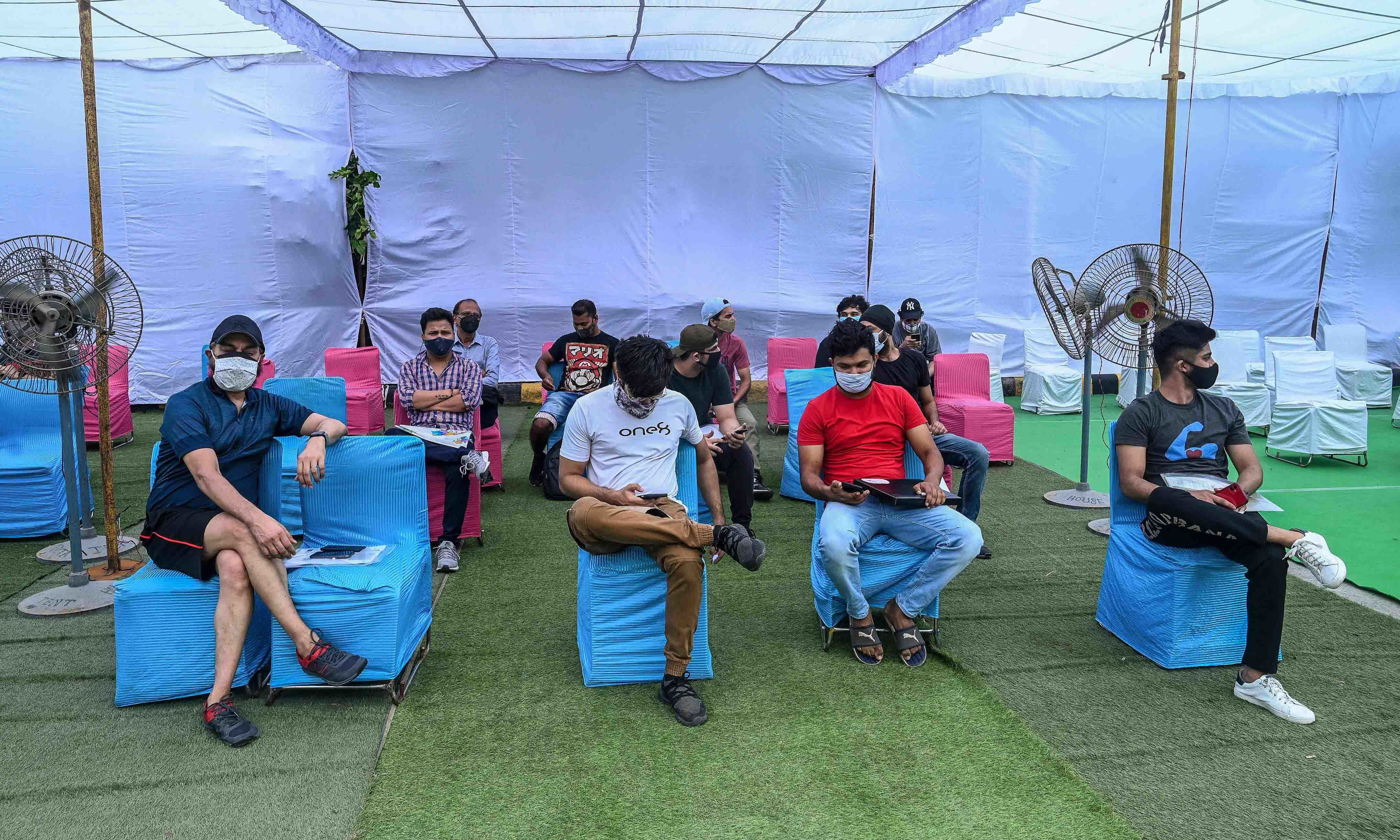 People wait to get vaccinated against the coronavirus at a dedicated vaccination centre for international travellers, in New Delhi on June 15. — AFP