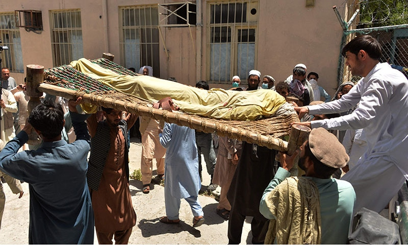 Relatives carry the body of a polio worker who was shot dead by gunmen in Nangarhar Province on Tuesday. — AFP