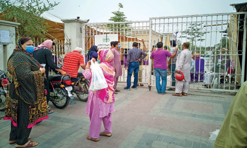 People stand outside the Covid-19 vaccination centre at Minar-i-Pakistan where the authorities have stopped vaccination due to a shortage of the vaccine. — White Star / Murtaza Ali
