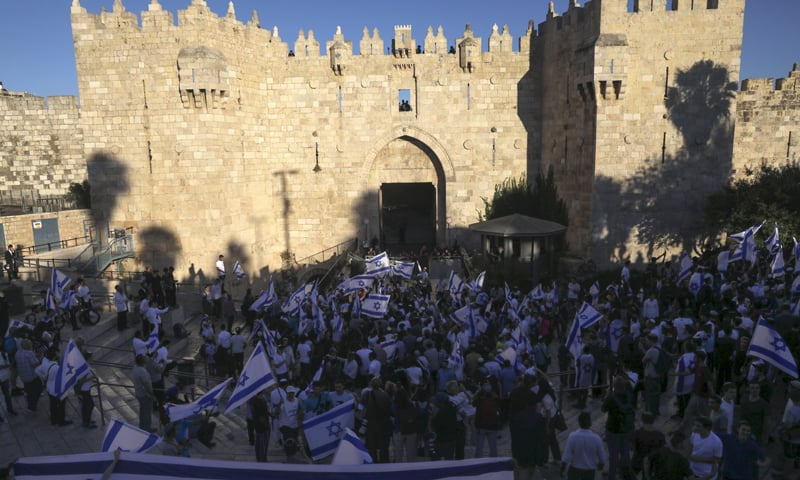 Jewish ultranationalists wave Israeli flags in the flag march next to Damascus Gate, outside Jerusalem's Old City. — AP