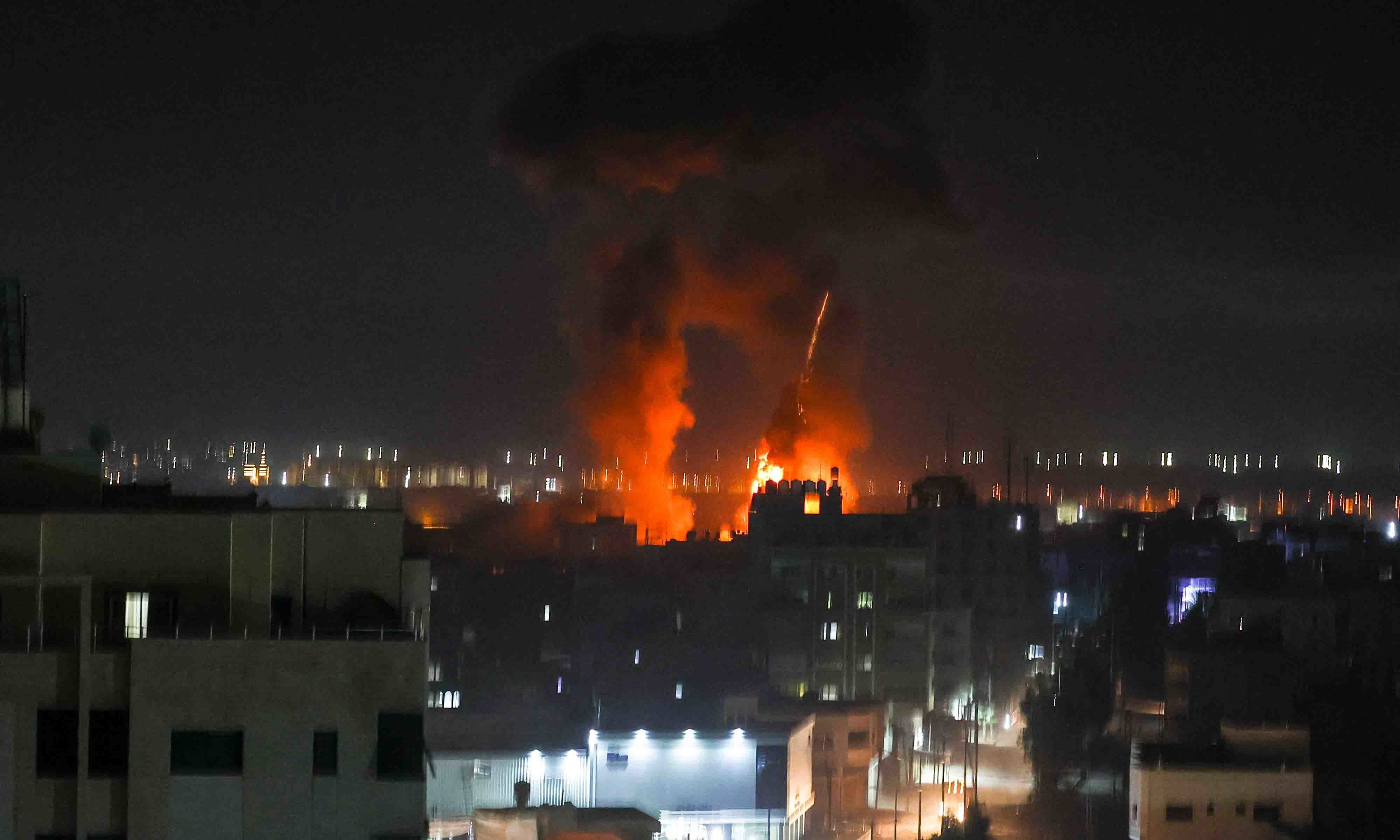 Explosions light-up the night sky above buildings in Gaza City as Israeli forces shell the Palestinian enclave, early on June 16. — AFP