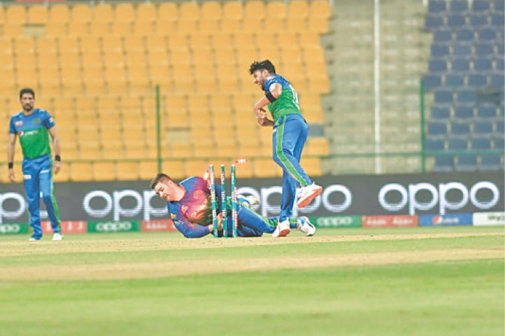 ABU DHABI: Multan Sultans' Rilee Rossouw breaks the stumps to run out Quetta Gladiators' opener Usman Khan (unseen) during their HBL Pakistan Super League match at the Sheikh Zayed Stadium on Wednesday night.—Courtesy PCB