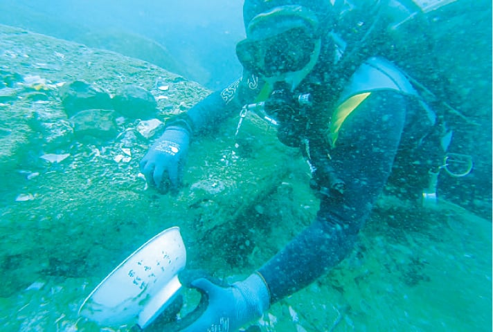 A DIVER holding a bowl with Chinese characters that was discovered from the shipwreck.—AFP