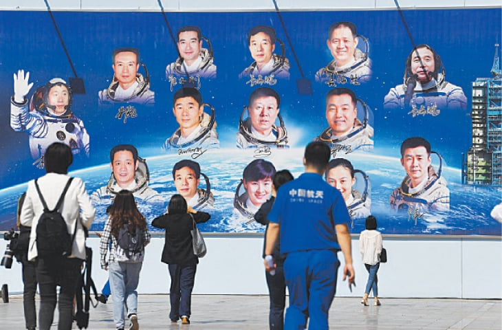 JOURNALISTS and staff walk towards a board displaying photos of astronauts at the Jiuquan satellite launch centre, in Gobi desert.—AFP