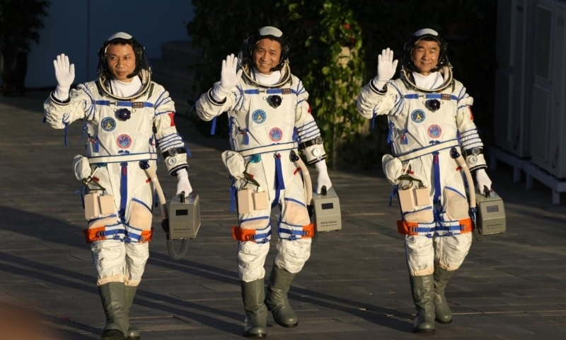 Chinese astronauts, from left, Tang Hongbo, Nie Haisheng, and Liu Boming wave as they prepare to board for liftoff at the Jiuquan Satellite Launch Centre in Jiuquan in northwestern China, June 17. — AP