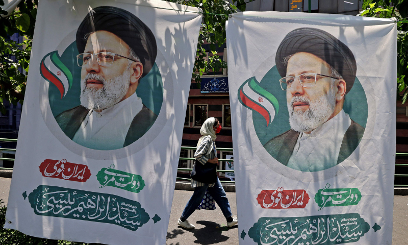 An Iranian woman walks past banners of ultraconservative cleric and presidential candidate Ebrahim Raisi, in Tehran, on Thursday, on the eve of the Islamic republic's presidential election. — AFP