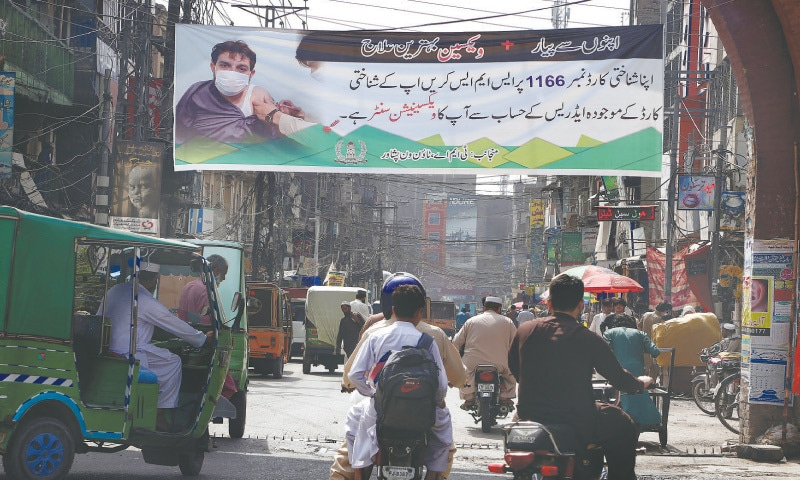 PESHAWAR: Motorcyclists on Thursday ride past a banner carrying details of the Covid-19 vaccination process, displayed over a market to encourage people to get vaccinated.—AP
