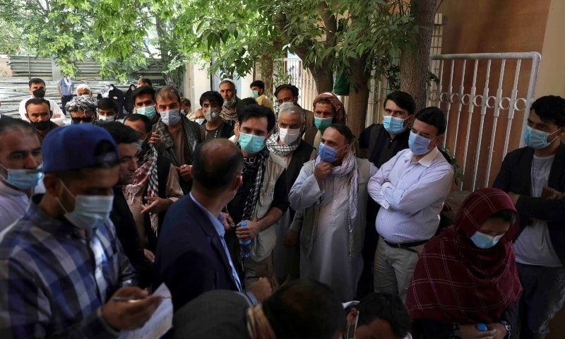 Residents, wearing face masks to help curb the spread of the coronavirus, line up to receive the Sinopharm Covid vaccine at a vaccination center, in Kabul on June 16. — AP