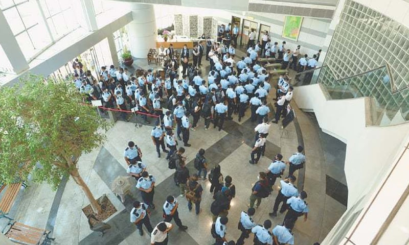 POLICE officers gather at the headquarters of Apple Daily.—Reuters