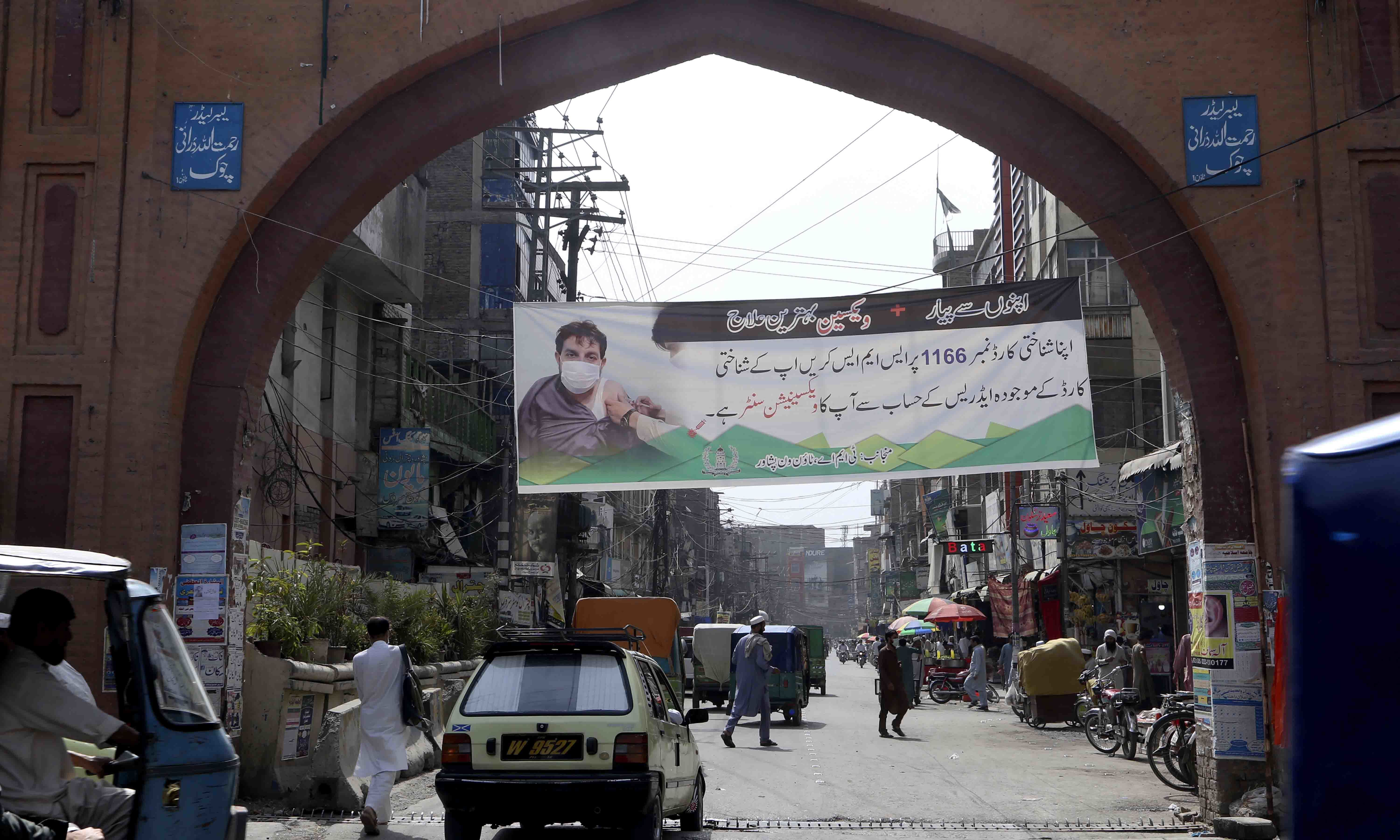 A banner giving details of the Covid-19 vaccination process is displayed on a market archway by local administration to encourage people to get vaccinated in Peshawar on June 17. — AP