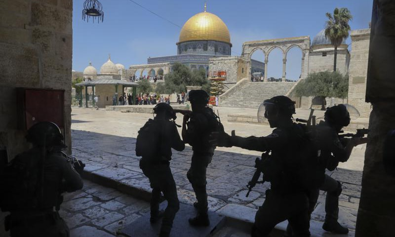 Israeli security forces take positions during clashes with Palestinians in front of the Dome of the Rock Mosque at the Al Aqsa Mosque compound in Jerusalem's Old City on Friday. — AP photo
