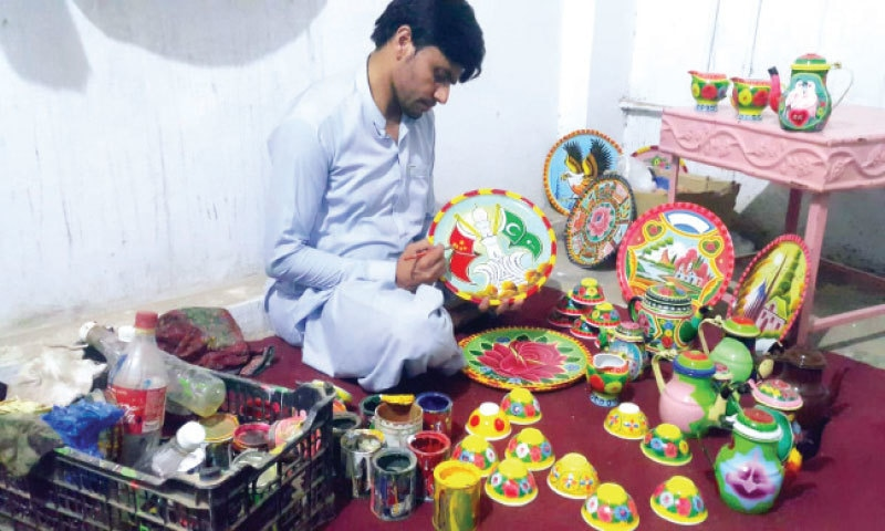 TRUCK artist Ismail Khan busy in work at his personal gallery. — Dawn